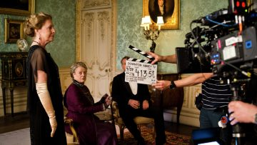 "From left: Penelope Wilton, Maggie Smith and Hugh Bonneville, behind the clapper board, on the set of ""Downton Abbey"" at Highclere Castle in Hampshire, England."